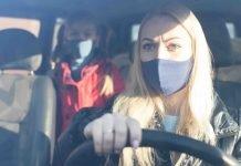 Persone in auto con mascherine (foto Shutterstock.com)