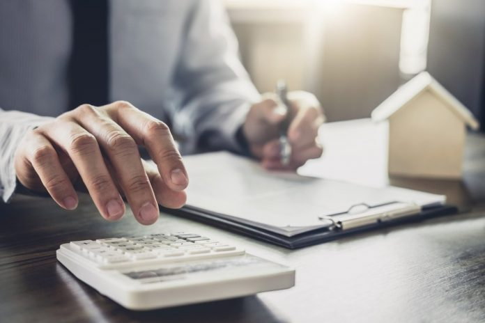 Un uomo al lavoro usa la calcolatrice (foto repertorio Shutterstock.com)