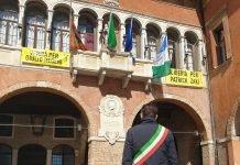 Il sindaco Gaffeo, davanti alla bandiera a mezz'asta, osserva un minuto di silenzio (foto dalla pagina Facebook del Comune di Rovigo)